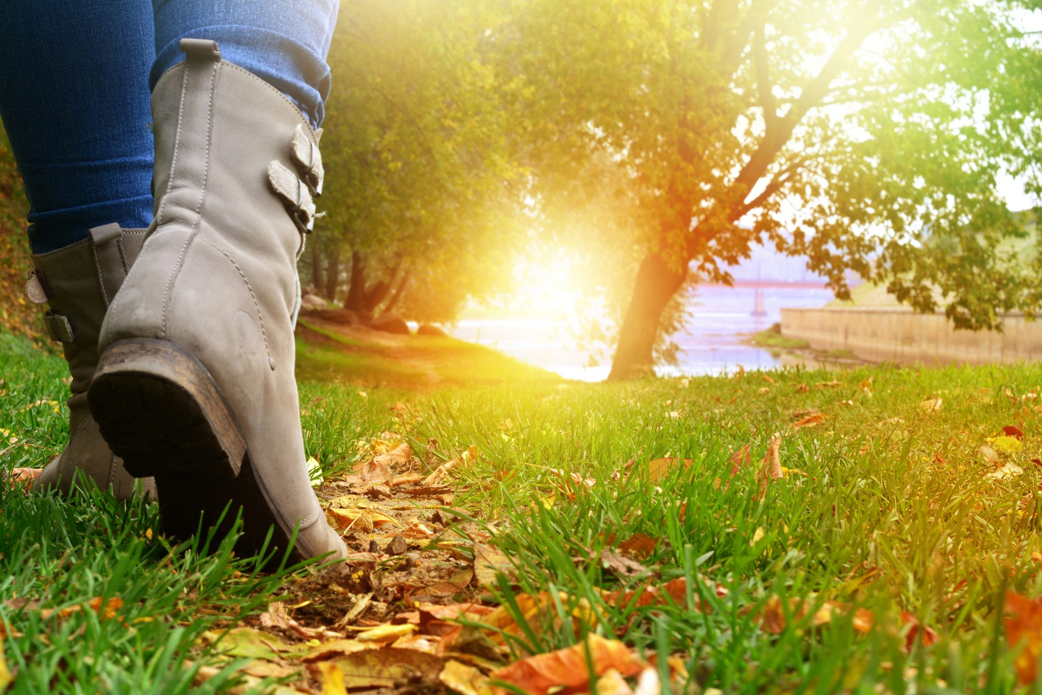 woman's boots walking through leaves on a path up a hill